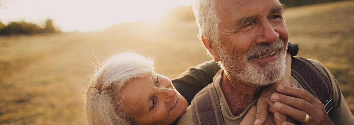 Two elderly people laughing and hugging in the middle of a field.