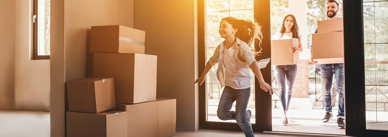 Chica corriendo dentro de una casa llena de cajas de cartón